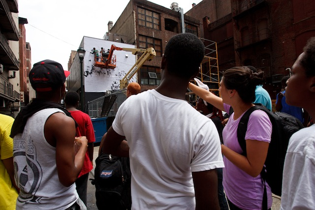 An art class from Mural Arts visits Vhils on site