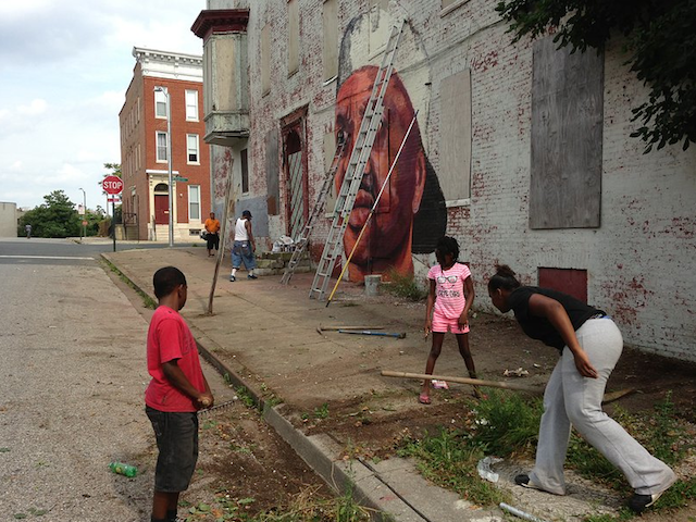Residents help cleaning up the block as Nanook Paints. 918 N. Arlington Street