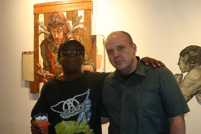 Shadow (left) and Andrew Michael Ford (right) in front of work from Elbowtoe and Armsrock. Photo from andrewmichaelford